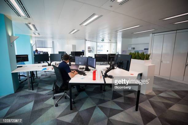 An employee sits at his desk at Cushman & Wakefield Plc's offices during the first phase of the reoccupation of their headquarters in London, U.K.,...