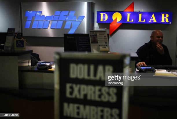 An employee sits behind a Dollar Thrifty Automotive Group Inc rental counter inside Louisville International Airport in Louisville Kentucky US on...