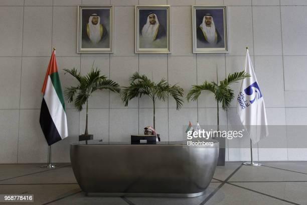 An employee sits beneath photographs of Sheikh Khalifa bin Zayed Al Nahyan United Arab Emirates' president and ruler of Abu Dhabi left Sheikh Zayed...