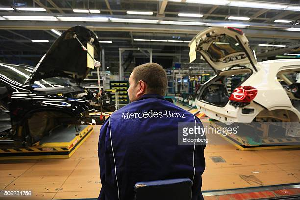 An employee sits beside MercedesBenz GLA compact SUV automobiles produced by Daimler AG as they move along the assembly line at the MercedesBenz...