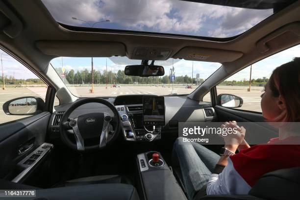 An employee sits in the passenger seat of a Toyota Motor Corp Prius hybrid car operated by YandexTaxi part of YandexNV as it take part in selfdriving...