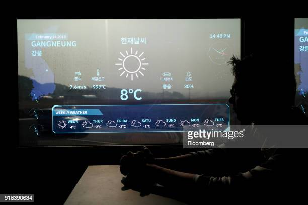 An employee sits next to a monitor displaying weather onboard an autonomous 5G connected bus operated by KT Corp as it travels along a road during a...
