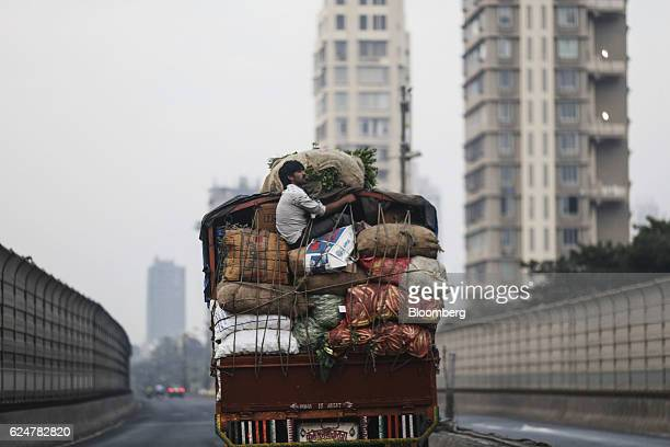 An employee sits on the back of a truck carrying vegetables as it travels along a highway in Mumbai India on Saturday Nov 19 2016 India's top court...