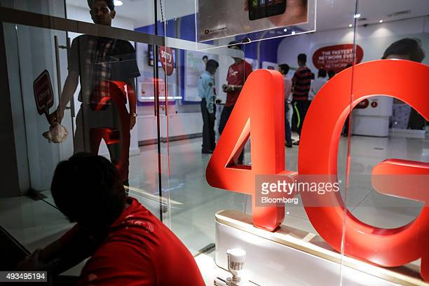 An employee sits outside a Bharti Airtel Ltd store in Mumbai India on Monday Oct 19 2015 Bharti Indias largest wireless carrier is scheduled to...