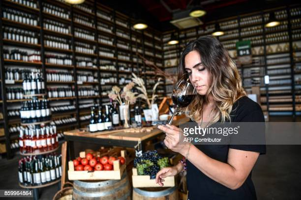 An employee smells a glass of wine on August 28 2017 at Suvla wine in Canakkale On the verdant fertile Gallipoli peninsula in northwest Turkey...