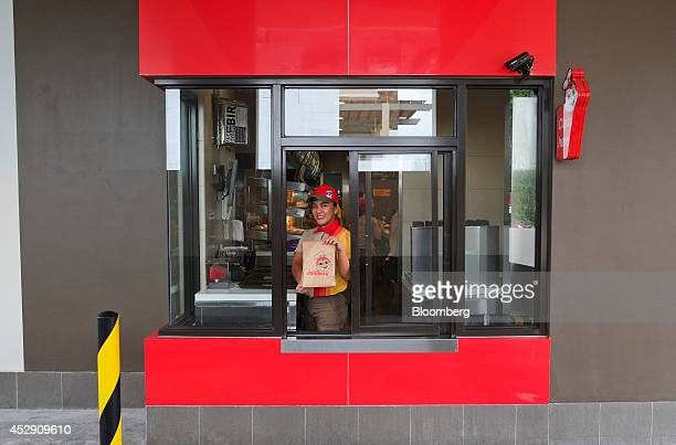 An employee smiles for a photograph while holding a customer's order in the drivethrough section of a Jollibee Foods Corp restaurant in Quezon City...
