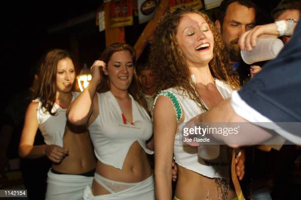 An employee soaks the shirts of competitors in a wet tshirt contest at Tequila Frogs in South Padre Island Texas March 18 2001 during the annual rite...