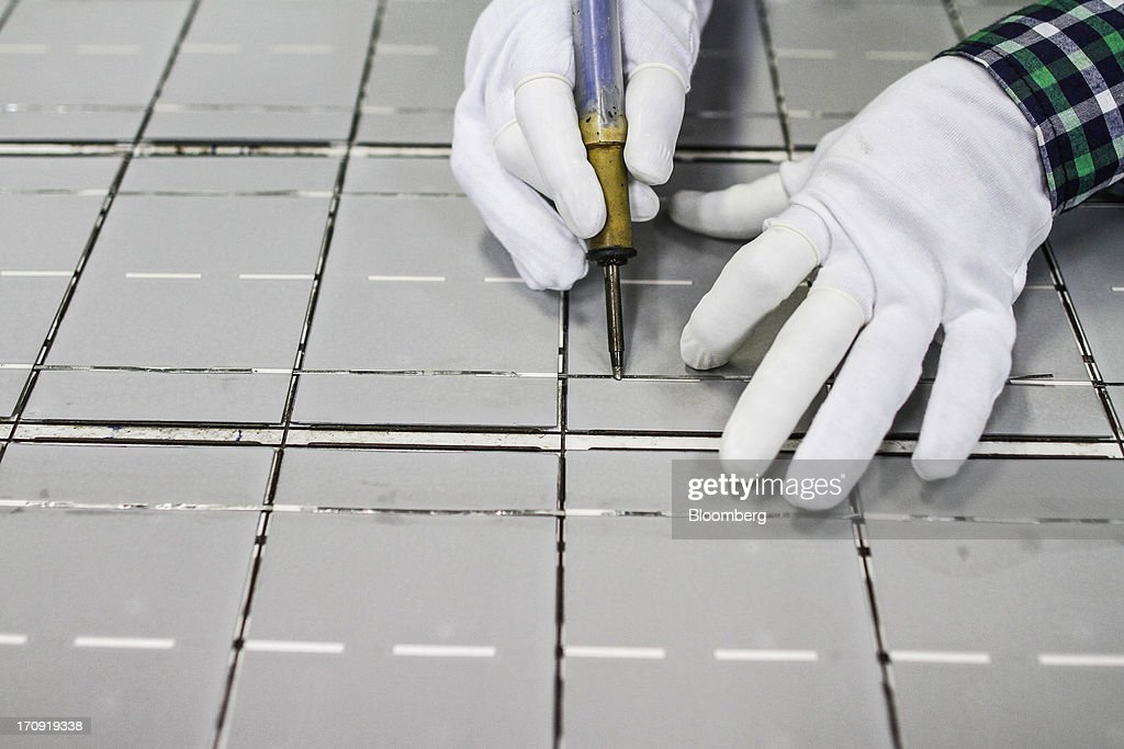An employee solders a solar panel on an assembly jig on the solar photovoltaic module production line at the Tata Power Solar Systems Ltd. manufacturing plant in Bangalore, India, on Tuesday, June 11, 2013. Tata Groups solar unit is expanding its business building plants for customers, forecasting that offices and factories will be paying more for grid power than solar by 2016 in most Indian states. Photographer: Dhiraj Singh/Bloomberg via Getty Images