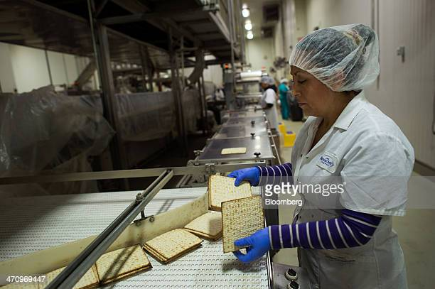 An employee sorts and stacks Passover matzo before it is wrapped at the Manischewitz Co factory in Newark New Jersey US on Thursday Feb 20 2014...