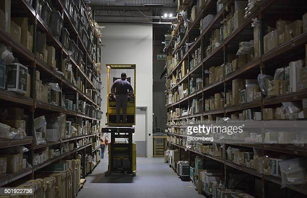 An employee sorts boxes of replacement parts for jets in the Dassault Aviation SA Falcon Jet parts distribution center at Teterboro Airport in...