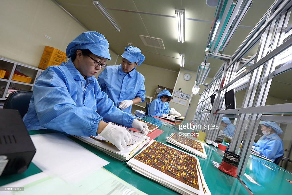 An employee sorts Flexible Printed Circuit Board (F-PCB) panels on the production line at the Seil Electronics Co. factory in Incheon, South Korea, on Wednesday, Aug. 28, 2013. South Korea has surpassed Brazil, Russia and India to become the second-biggest emerging stock market for the first time since 2006, as a stable won and record current-account surplus lure investors. Photographer: SeongJoon Cho/Bloomberg via Getty Images