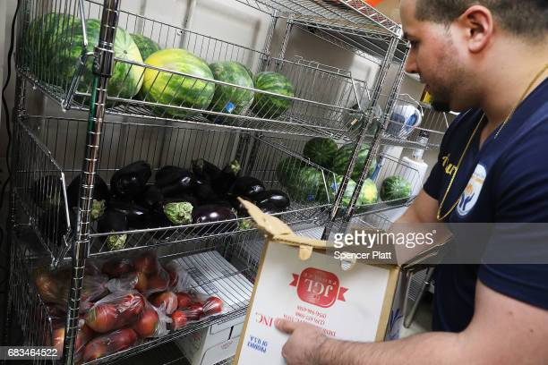 An employee sorts food at the Reaching Out Community Services food pantry in Brooklyn on May 15 2017 in New York City The popular Brooklyn food...