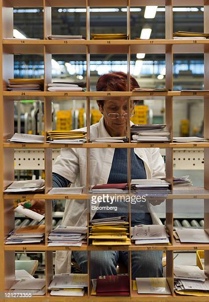 An employee sorts mail by hand at Deutsche Post AG's sorting facility in Munich Germany on Tuesday Aug 16 2011 Deutsche Post AG is the world's...