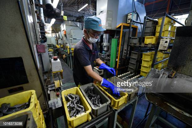 An employee sorts vehicle parts at an Asahi Tekko Co factory in Nishio Aichi Prefecture Japan on Wednesday Aug 1 2018 Japan's government announced...