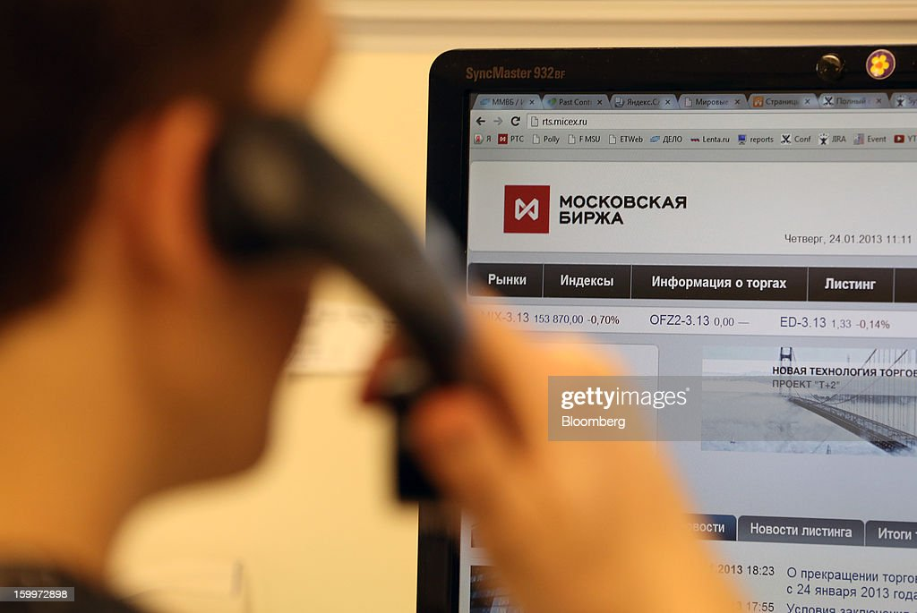 An employee speaks on the phone in front of a computer screen displaying a website at the Moscow Exchange in Moscow, Russia, on Thursday, Jan. 24, 2013. The Moscow Exchange, Russia's biggest bourse, plans to raise more than $500 million in an initial public offering, according to a person with knowledge of the matter. Photographer: Andrey Rudakov/Bloomberg via Getty Images