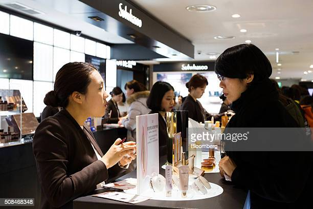 An employee speaks to a customer at a cosmetics booth in a Hotel Lotte Co Duty Free store in Seoul South Korea on Thursday Feb 4 2016 Hotel Lotte the...