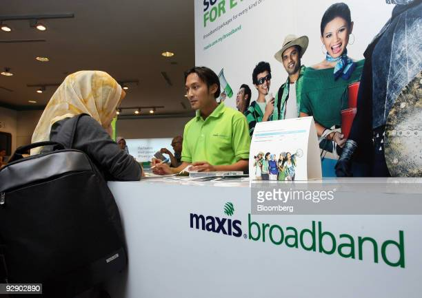 An employee speaks to a customer at the counter for broadband Internet at the Maxis service center in Kuala Lumpur City Centre in Kuala Lumpur...