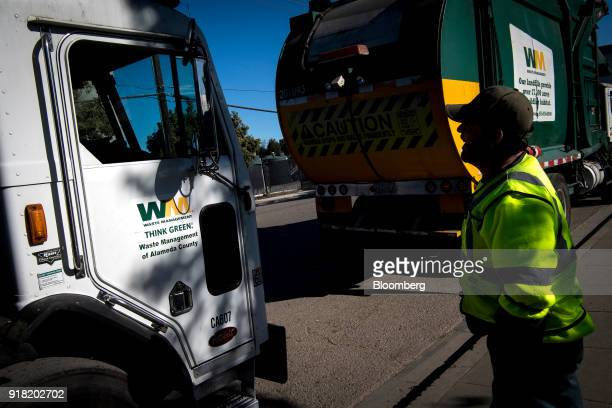 An employee speaks to the driver of a Waste Management Inc garbage collection truck outside the company's Davis Street Recycling Transfer Station in...