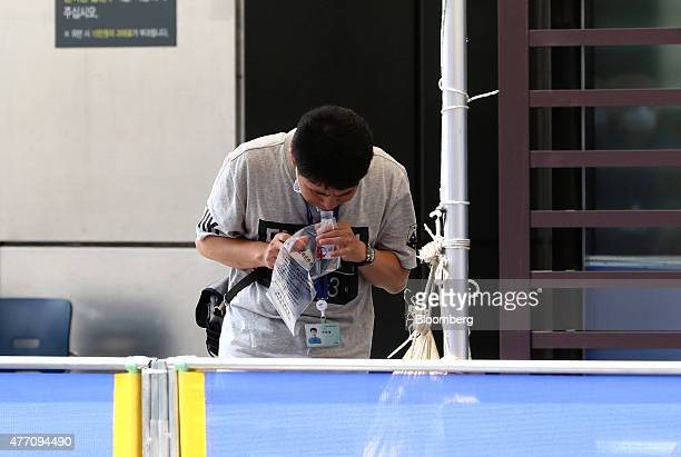 An employee spits into a container to obtain a saliva sample to test for Middle East Respiratory Syndrome infection at the Samsung Medical Center in...