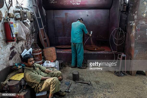 An employee spray paints a part for a centrifugal air blower at a booth inside an Ishwar Engineering Co factory in Mumbai Maharashtra India on...