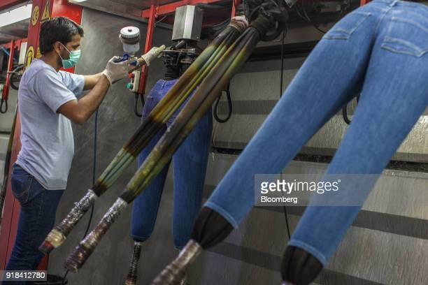 An employee sprays a pair of jeans at the Artistic Denim Mills Ltd factory in Karachi Pakistan on Tuesday Feb 6 2018 Pakistans manufacturers have...
