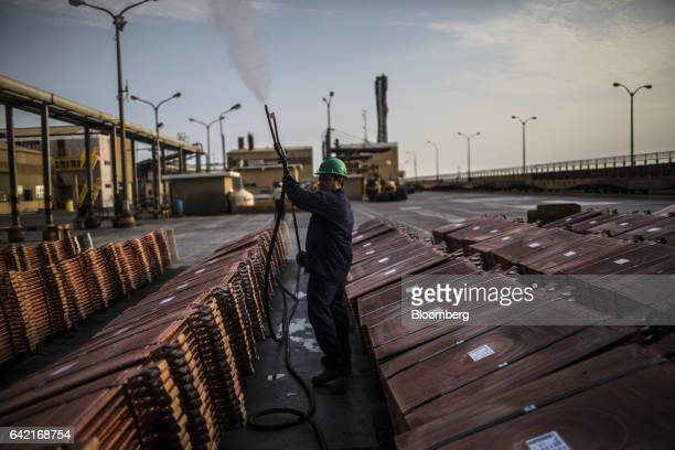 An employee sprays antioxidant solution on a pile of copper plates at the Southern Copper Corp refinery in Ilo Peru on Thursday Jan 26 2017 Peru...