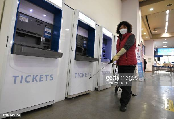 An employee sprays disinfectant at a railway station in the southeastern city of Daegu on February 21, 2020 - South Korea confirmed 52 more cases of...