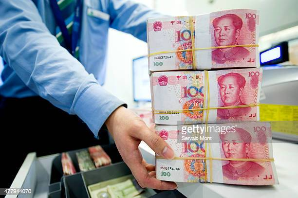 An employee stacks Chinese Yuan bank notes in a Standard Chartered bank branch, on May 13 in Shanghai, China. Aiming for more access to the global...