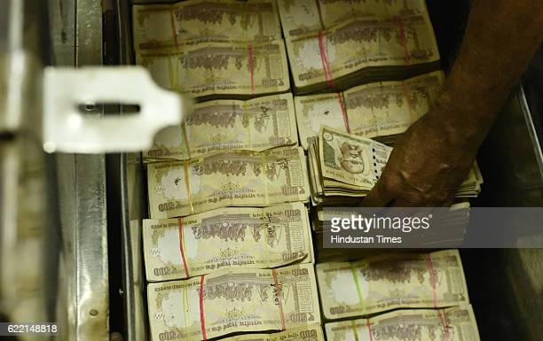 An employee stacks old currency notes at an exchange counter at Allahabad Bank branch of Parliament Street on November 10 2016 in New Delhi India It...