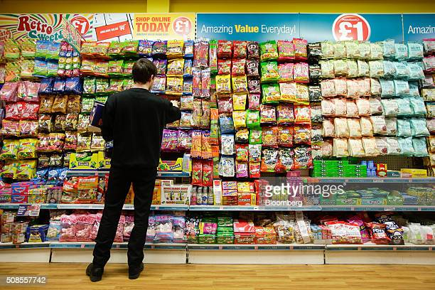 An employee stacks snacks at a Poundland Group Plc store in Leigh UK on Thursday Feb 4 2016 UK like for like sales at midmarket retailers rose 14...