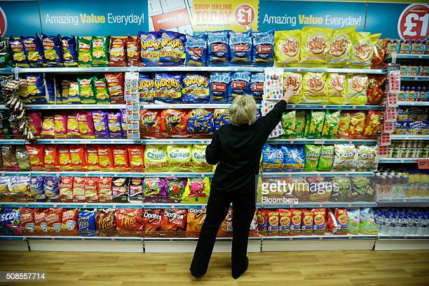 An employee stacks the shelves with snack products at a Poundland Group Plc store in Leigh UK on Thursday Feb 4 2016 UK like for like sales at...