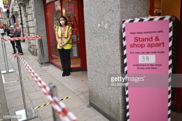 An employee staffs the door to manage queueing at a TK Maxx store in York northern England on June 15 2020 as some nonessential retailers reopen from...