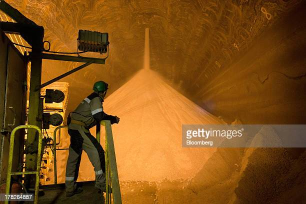 An employee stands and watches as potash grain falls from a hole in the ceiling into an underground storage area inside a potash mine operated by OAO...