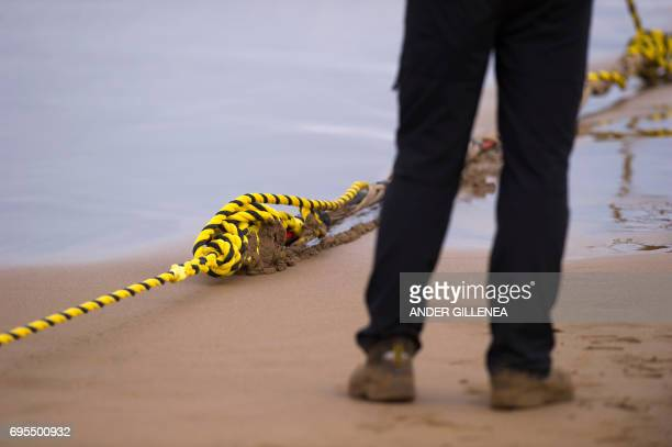 An employee stands as he lays an undersea fiber optic cable at Arrietara beach near the Spanish Basque village of Sopelana on June 13 2017 Facebook...