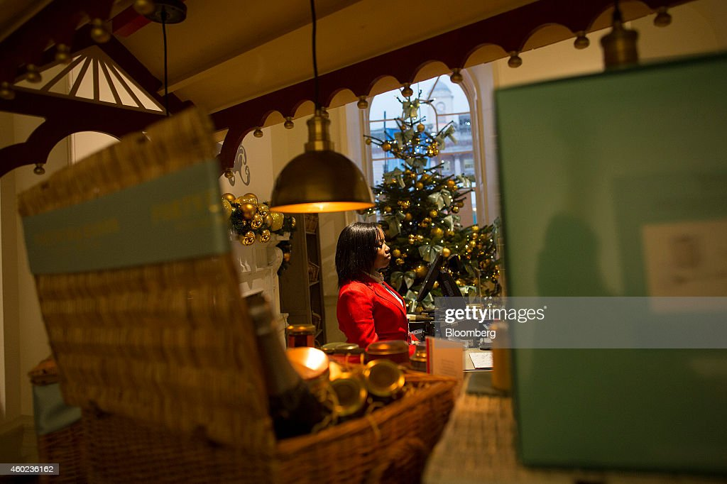An employee stands at a checkout beside a decorated Christmas tree inside a pop-up store, operated by Fortnum & Mason Plc, during a seasonal Christmas event at Somerset House in London, U.K., on Tuesday, Dec. 9, 2014. The British will be the biggest spenders in Europe on Christmas gifts this year, according to a study commissioned by Dutch bank ING Groep NV. Photographer: Simon Dawson/Bloomberg via Getty Images