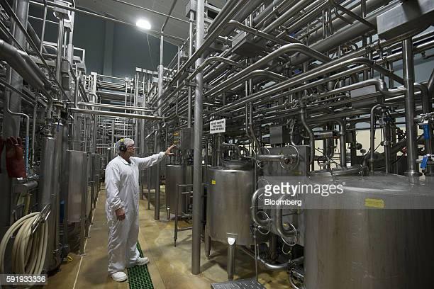 An employee stands at a control panel next to machinery on the milk powder production line at a Fonterra Cooperative Group Ltd factory in Kauri New...