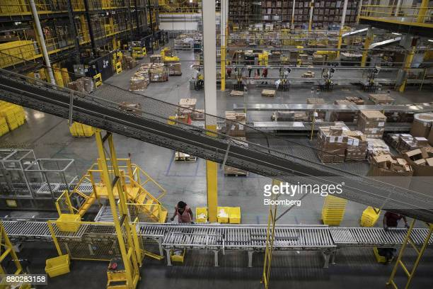 An employee stands at a conveyor belt inside the Amazoncom Inc fulfillment center in Robbinsville New Jersey US on Monday Nov 27 2017 The holiday...