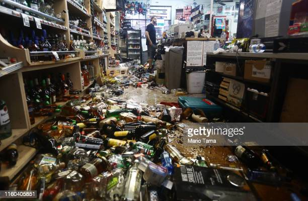 An employee stands at the register as broken bottles are scattered on the floor in Eastridge Market following a 71 magnitude earthquake which struck...