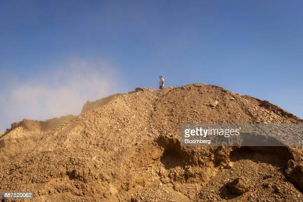 An employee stands atop a pile of clay in a preparation unit at the Shabbir Tiles Ceramics Ltd production facility in Karachi Pakistan on Wednesday...