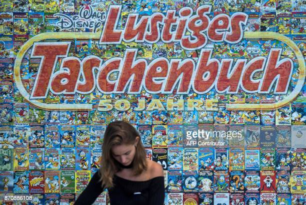 An employee stands behind a cashier desk in front of a backdrop made up of hundreds of covers of Donald Duck pocket books called 'Lustiges...