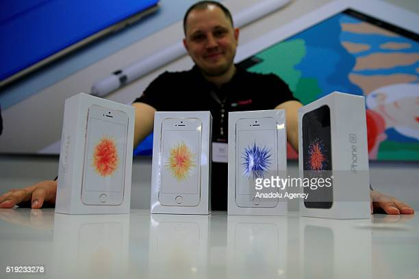 An employee stands behind Apple phone at a shop after Apple launched iPhone SE in Moscow Russia on April 5 2016