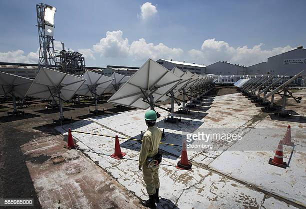 An employee stands behind heliostats at Mitsubishi Hitachi Power Systems Ltd's solar thermal power system verification testing facility at the MHPS...