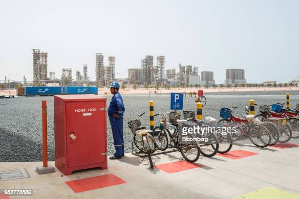 An employee stands beside a fire hose box and bicycle park at the Ruwais refinery and petrochemical complex operated by Abu Dhabi National Oil Co in...