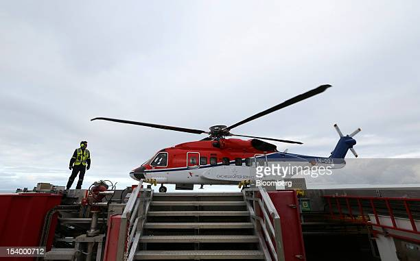 An employee stands beside a Sikorsky Aircraft Corp S92 helicopter operated by CHC Helicopter Services on the helipad at the Troll A offshore gas...
