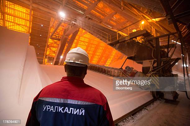 An employee stands beside stores of potassium chloride also known as potash at a storage plant operated by OAO Uralkali in Berezniki Russia on Friday...