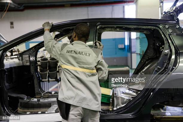 An employee stands beside the body shell of a Nissan Micra automobile on the assembly line inside the Renault SA factory in Flins France on Thursday...