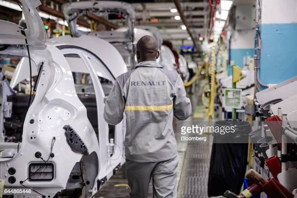 An employee stands beside the body shell of a Renault Zoe automobile on the assembly line inside the Renault SA factory in Flins France on Thursday...