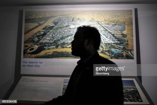 An employee stands in front of a display in a Lodha Group showroom in Palava City on the outskirts of Mumbai India on Thursday May 25 2017 Lodha best...