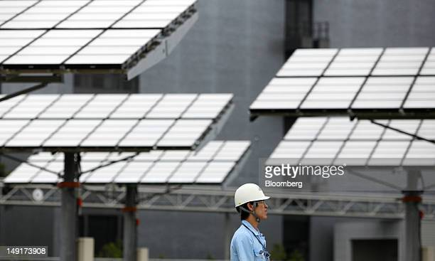 An employee stands in front of concentrator photovoltaic units at Sumitomo Electric Industries Ltd's new power plant in Yokohama Japan on Tuesday...