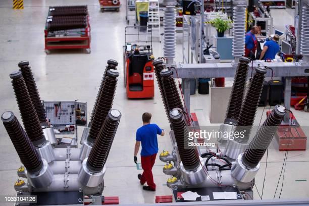 An employee stands near dead tank circuit breakers inside Siemens AG switchgear electronic power unit factory in Berlin Germany on Thursday Sept 13...